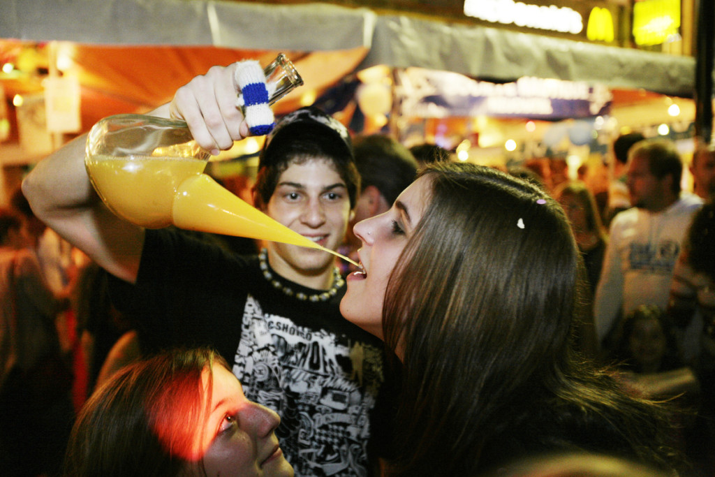 Grape Harvest Festival in Neuchâtel. A young boy offers to a young girl a mixing of orange juice and strong alcohol drinks. - 2006